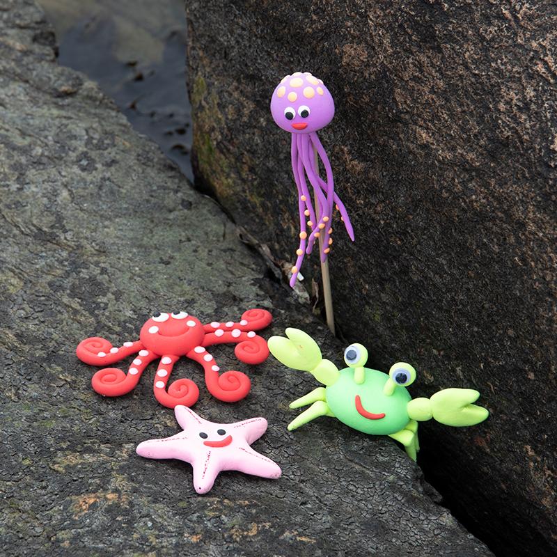 Lag blekksprut, manet, sjøstjerne og krabbe av leire