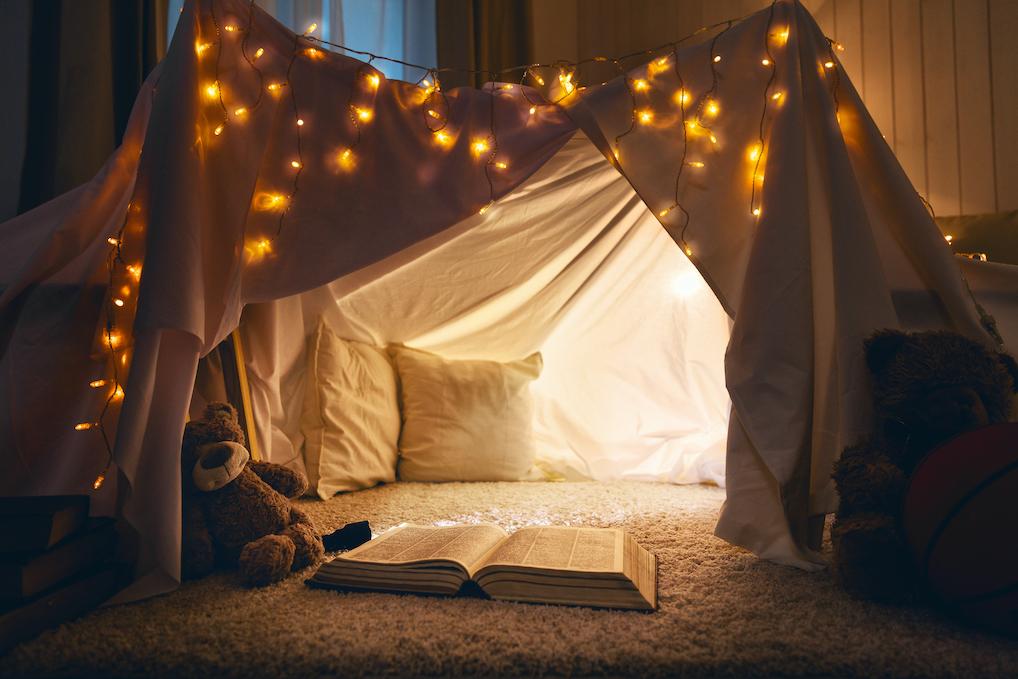 Mysigt tält som står på en matta och är upplyst med ljusslinga